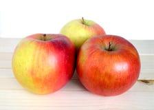3 зрелых красных яблока в бежевом деревянном крупном плане полки Стоковые Фотографии RF