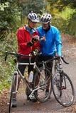 2 зрелых мужских велосипедиста на езде смотря мобильный телефон App Стоковое Изображение RF