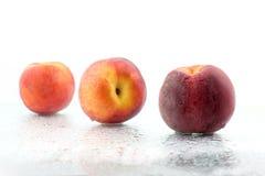 3 зрелых персика в капельках воды на белой предпосылке Стоковое Изображение