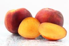 2 зрелых персика в капельках воды на белой предпосылке Стоковые Изображения