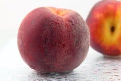 2 зрелых персика в капельках воды на белой предпосылке Стоковое Изображение