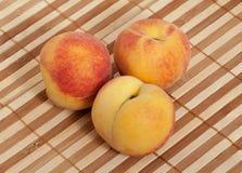 3 зрелых персика на плетеной циновке соломы Стоковое Фото