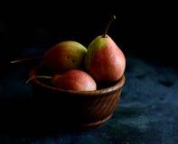 3 зрелых сочных груши в коричневой плите на темной предпосылке Стоковая Фотография