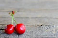 2 зрелых сладостных вишни изолированной на винтажной деревянной предпосылке с пустым космосом для текста Стоковое Изображение