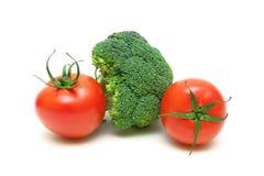 2 зрелых томаты и брокколи на белой предпосылке Стоковые Изображения RF