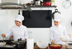 2 зрелых шеф-повара женщин варя еду на кухне Стоковое Изображение RF