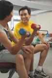 2 зрелых люд поднимая весы в спортзале Стоковое Изображение