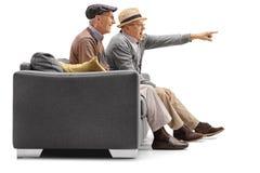 2 зрелых люд сидя на кресле с одним из их указывая Стоковое Изображение RF