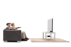 2 зрелых люд сидя на софе и смотря телевидение Стоковые Фотографии RF
