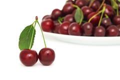 2 зрелых ягоды с зелеными лист и плитой (изолированной) вишни Стоковые Изображения RF