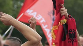 Зрители футбола держа флаги албанца и поддерживая их команду на спичке акции видеоматериалы