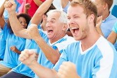 Зрители в цветах команды наблюдая событие спорт Стоковое Изображение