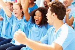 Зрители в цветах команды наблюдая событие спорт Стоковое Фото