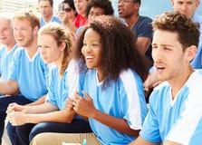 Зрители в цветах команды наблюдая событие спорт Стоковое фото RF