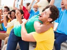 Зрители спорт в цветах команды празднуя Стоковое Фото