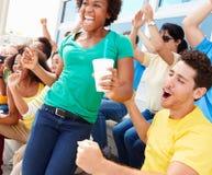 Зрители спорт в цветах команды празднуя Стоковая Фотография RF