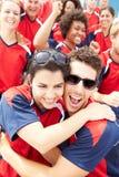 Зрители спорт в цветах команды празднуя Стоковые Фото