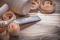 Зубила деревянного молотка более твердые завили shavings на винтажной деревянной горжетке Стоковое Изображение