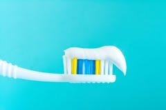 Зубная паста на конце-вверх зубной щетки на голубой предпосылке Стоковое фото RF