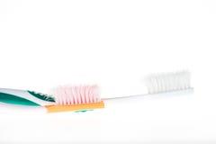 2 зубная щетка несенная цветами на изолированной белой предпосылке Стоковая Фотография