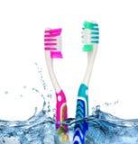 2 зубной щетки в воде на белой предпосылке Стоковая Фотография