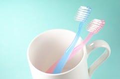 2 зубной щетки и чашка. Стоковое Изображение