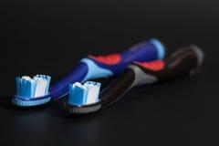 2 зубной щетки на черноте Стоковое Фото