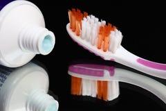 Зубные щетки и зубная паста на полке зеркала Продукты гигиены полости рта стоковое фото rf