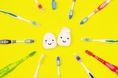 Зубные щетки и зубоврачебная зубочистка на желтой предпосылке стоковые изображения rf