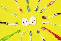 Зубные щетки и зубоврачебная зубочистка на желтой предпосылке стоковое фото