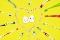 Зубные щетки и зубоврачебная зубочистка на желтой предпосылке стоковые фото