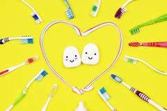 Зубные щетки и зубоврачебная зубочистка на желтой предпосылке стоковое фото rf