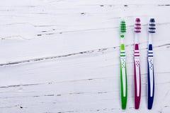 Зубные щетки на белой деревянной предпосылке Стоковые Изображения RF