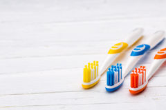 Зубные щетки на белой деревянной предпосылке Стоковые Фотографии RF
