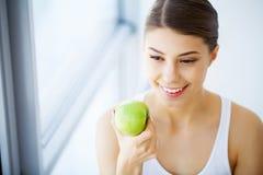 Зубоврачебная внимательность Женщина с зеленым яблоком стоковое фото