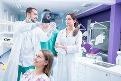 Зубоврачебная медицинская бригада рассматривая и работая на молодом pati ¸female стоковые изображения rf