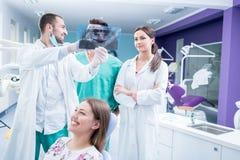 Зубоврачебная медицинская бригада рассматривая и работая на молодом pati ¸female стоковое фото