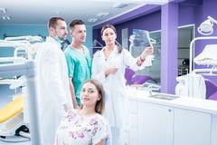Зубоврачебная медицинская бригада рассматривая и работая на молодом pati ¸female стоковое изображение rf