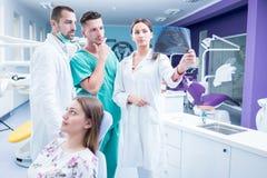 Зубоврачебная медицинская бригада рассматривая и работая на молодом pati ¸female стоковая фотография rf