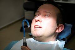 Зубоврачебная проверка вверх Зубоврачебный мужской пациент на регулярн зубоврачебной проверке, на зубоврачебных клинике и офисе Ч стоковое фото