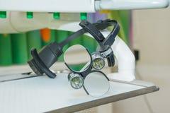 Зубоврачебные бинокулярные loupes на белом tablel в зубоврачебном офисе Изумлённые взгляды дантиста, защитные стекла в офисе ` s  Стоковые Фото