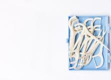 Зубоврачебные flossers на предпосылке белой бумаги стоковое фото