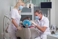Зубоврачебный офис, доктор рассматривает пациента, ассистентской помощи на рассмотрении стоковая фотография rf