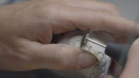 Зубоврачебный техник держа искусственную прессформу челюсти с зубами и полируя их в лаборатории Зубы дантиста чистя щеткой с проф акции видеоматериалы
