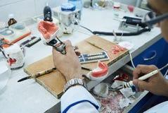 Зубоврачебный техник или дантист работая с dentures зуба стоковая фотография rf