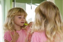 Зубы белокурой девушки чистя щеткой Стоковая Фотография