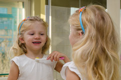 Зубы белокурой девушки чистя щеткой Стоковая Фотография RF