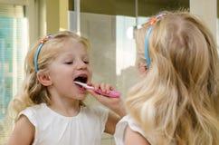 Зубы белокурой девушки чистя щеткой Стоковые Фото
