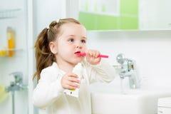 Зубы девушки ребенка чистя щеткой в ванной комнате Стоковая Фотография RF