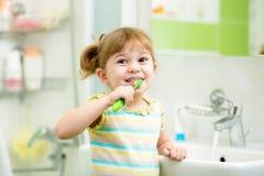 Зубы девушки ребенк чистя щеткой в ванной комнате Стоковая Фотография RF